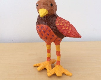 Red and brown papier-mache bird sculpture with yellow and red striped legs