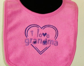 Embroidered baby bib with saying *I love Grandma* in pink and purple