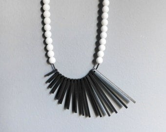 minimalist geometric necklace with black sticks and white beads - contemporary jewelry