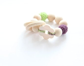 Green flower teething toy with crochet wooden beads and 2 wooden rings. Violet and light green wooden beads rattle.
