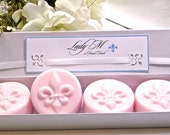 A quatuor of small round soaps decorated with a lily,  guest size. 4 soaps with a roses fragrance.