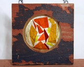 Antique painted pine flooring with yellow, orange and red stained glass shards, laid over white sea glass.