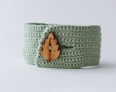 Soft green crochet cuff bracelet with wooden leaf button
