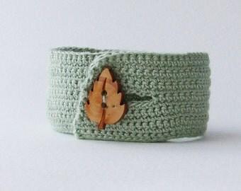 Soft green crochet cuff bracelet with wooden leaf button