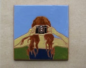 Handmade ceramic tile with a girl taking a photo