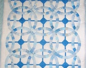 Double Wedding Ring Crib Size Quilt in shades of blue, over underlying blue square pattern