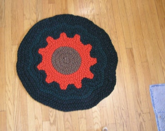 This is a round handmade braided rug with an orange sunflower in the center.