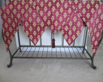 Five piece custom made dark red with gold pattern lined damask valance points with center tassel for window cornice