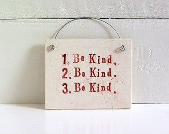 1. Be Kind.  2. Be Kind.  3. Be Kind.   Hand Made Ceramic Wall Sign.  That Is All.