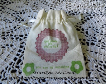 """Darling cottage-style cream muslin drawstring gift bag 4""""x5-1/2"""" with ink stamped rose scalloped circle frame image with silver glitter.."""