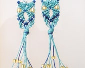 Turquoise and navy blue owl micro macrame earrings with glowing golden eyes and beaded fringe