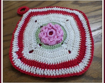 Center flowered pot holder crocheted with pink, green, red, and white cotton yarn.