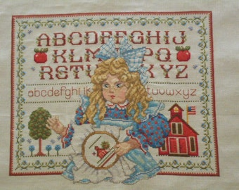 Finished Counted cross stitch. Doll in schoolhouse sampler.