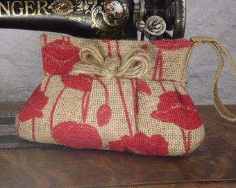 Burlap wristlet clutch with red poppy flowers and jute bow embellishment
