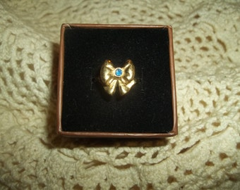 Avon Signed Golden Bow Ring With A Small Blue Cubic Zirconia Stone