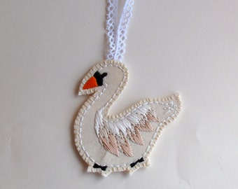 Christmas swan ornament hand embroidered on cream muslin