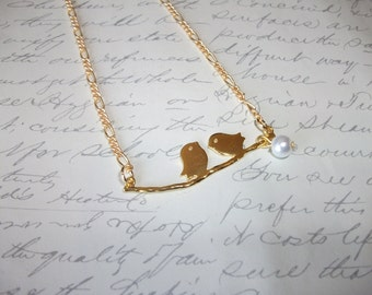Gold birds on branch with pearl necklace