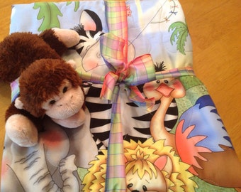 Jungle quilt with little stuffed animal.