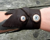Hand sewn leather bracelet with blue eyes