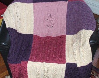 Beautiful hand knit blanket or afghan with a rose colored tree motif in the center and different knit designs in the other panels