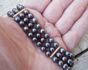 Triple strand black pearl bracelet in 14kt.