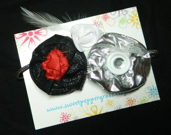 Adorable girl, toddler stretchy headband bow with sparkle ribbon, black and shiney silver flower, and white rosette with feather