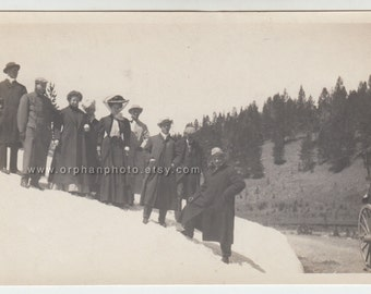 Vintage/Antique beautiful photo women and men in suits, coats, dresses and hats standing on a snowy mountain side