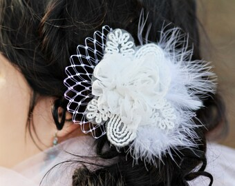 Bridal hair flower, white flower accented with feathers and netting. Placed on an alligator clip or satin ribbon.