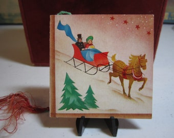 Colorful unused 1940's-50's Christmas themed bridge tally card victorian dressed man and woman in horse drawn sleigh