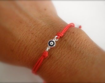 blue evil eye bracelet on a red string