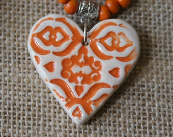 Orange ceramic heart necklace with wooden beads.