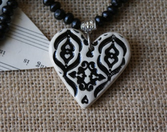 Black ceramic heart necklace with wooden beads.