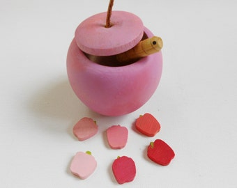 Pink wooden apple box with worm and little apples