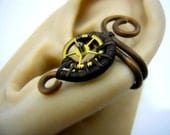 Watch Gear Earcuff, a small Steampunk Ear Cuff made from black patina copper wire and Gold Colored Watch Gear