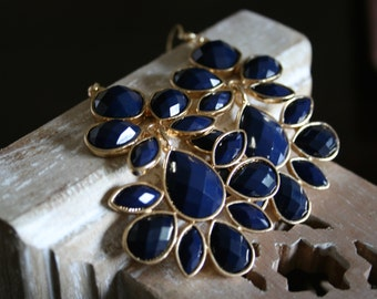 Large royal blue chandelier earrings in a gold setting