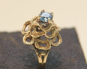 An attractive 9 ct solid gold dress ring with a light-blue center stone