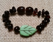 dark cherry baltic amber teething bracelet with green leaf accent