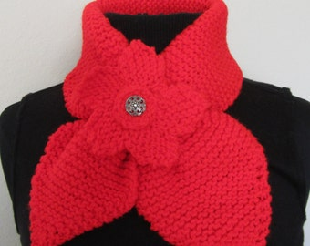 Scarf- Neck Warmer knitted with acrylic yarn decorated with a matching red flower with a silver glittery scrolled button in its center.