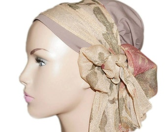 Taupe turban adorned with a large glittered band made of veil embellished with golden, burgundy and green printed flowers.