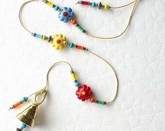 Beaded Garden Chime. Daisy Wind Chime. Flowers. Colorful. Daisy Beads. Blue. Yellow. Green. Orange. Retro Daisy. Funky Flowers. Brass Bell