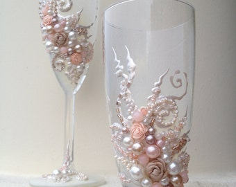 Beautiful wedding champagne glasses in blush pink, ivory and champagne, elegant toasting flutes with pearls and roses