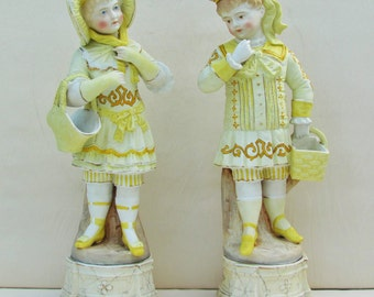 Pair of antique bisque figurines, Victorian boy and girl with baskets, late 1800's porcelain figurines