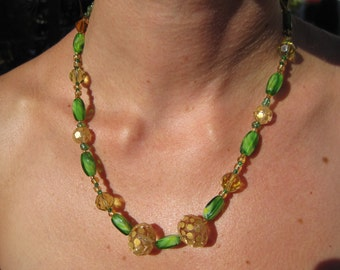 Elegant handmade necklace with gold and green glass beads and a toggle clasp.