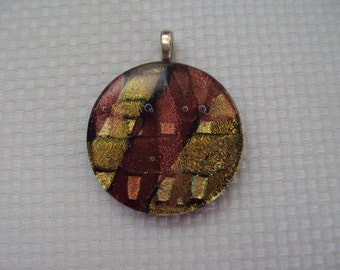"""Round fused glass pendant. Gold plated bail, black glass with org/brown/gold dichroic glass. Size is 1 3/4"""".  PM004"""