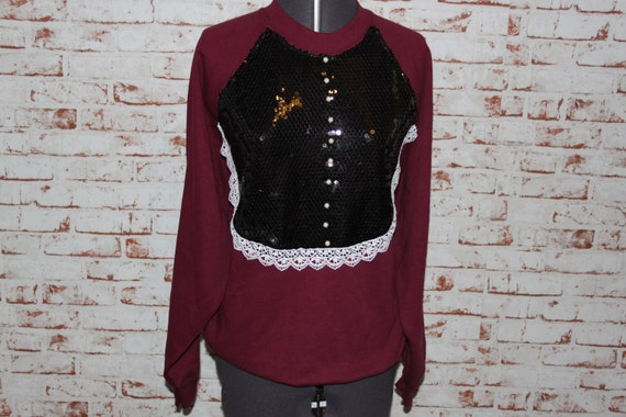 Burgundy jumper, black sequin bib with white lace trim and pearls. Size - Large.
