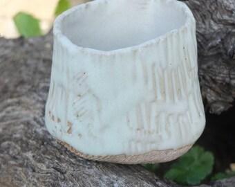 Pot embossed and glazed. Celadon. Bottom embossed, not enamelled