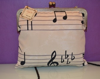 bag stamped with musical motifs and kiss clasp