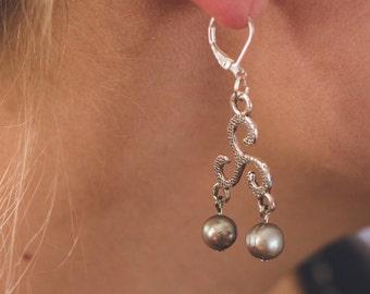 celtic swirl earrings with 2 grey pearls dangling for each.
