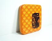 tile with a Rolleiflex camera on a screenprinted clementine scallop pattern on orange, made to order.