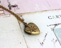 snowflake. heart locket necklace. in gold ox with etched lines locket